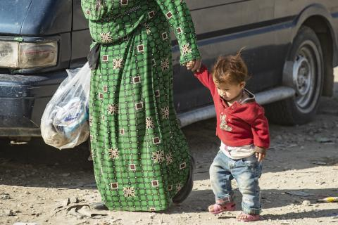 a child walking next to his mother