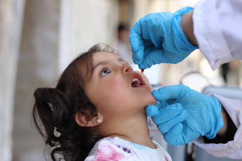 A girl being vaccinated via mouth drops