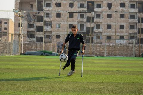 a boy on crutches playing football