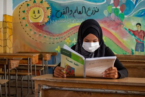 Nuha, 16, reads from her Arabic language textbook.