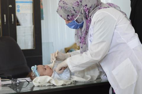 a health worker checking a baby girl