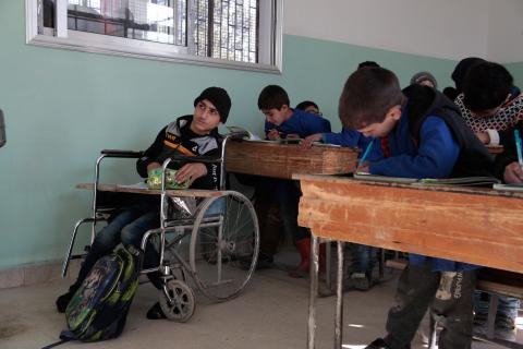 a boy in a wheelchair in a a classroom