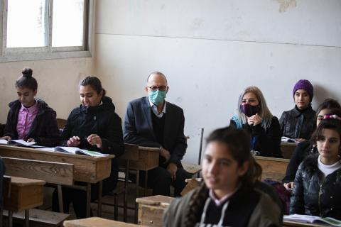 Chaiban wearing a mask and sitting in a class room with children