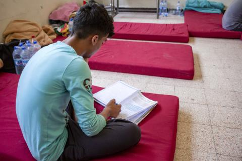 a boy sitting on a floor matress studying