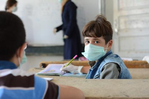 a boy wearing a mask in a classroom