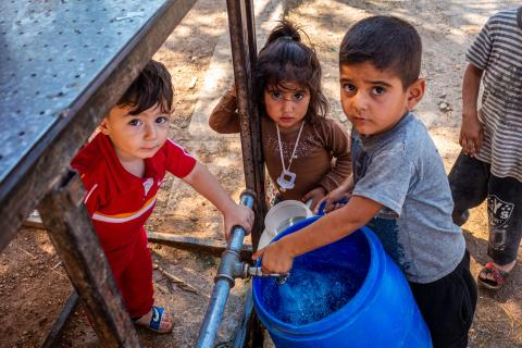Children fil buckets and jerry cans from a UNICEF-supported water tanks in Fafin village, northern rural Aleppo..