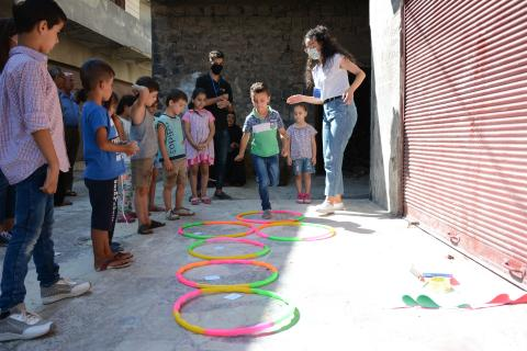 a group of children playing with a volunteer guiding them