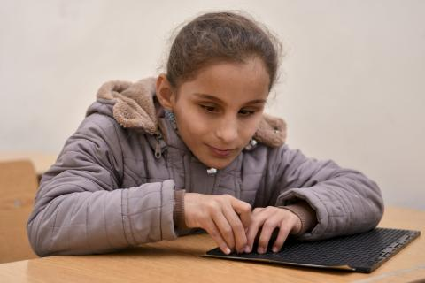a blind girl reading in braille