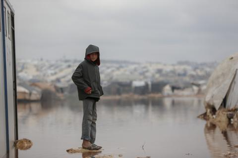 A boy standing in the middle of puddled camp