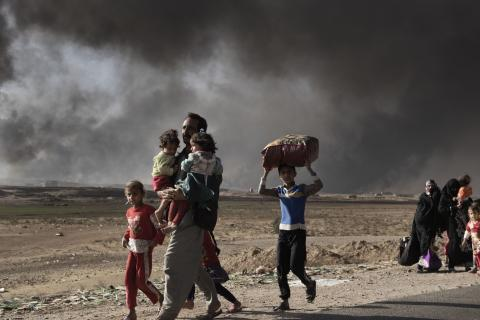 displaced man carries two children