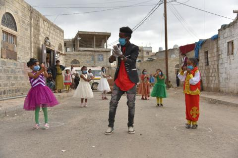 kids and a volunteer performing in street with masks