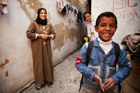 a boy carrying a backpack with his mother nad sister in the background