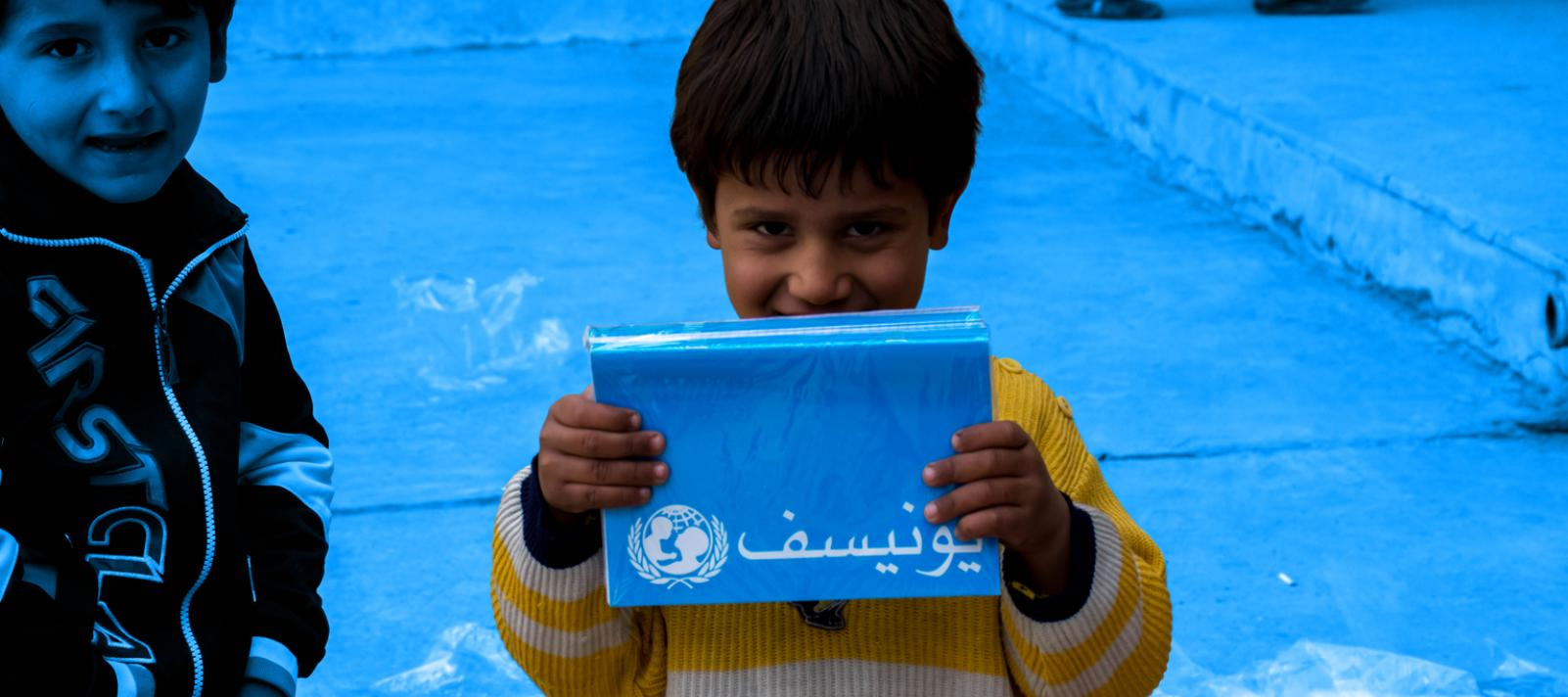A child holding a UNICEF branded notebook