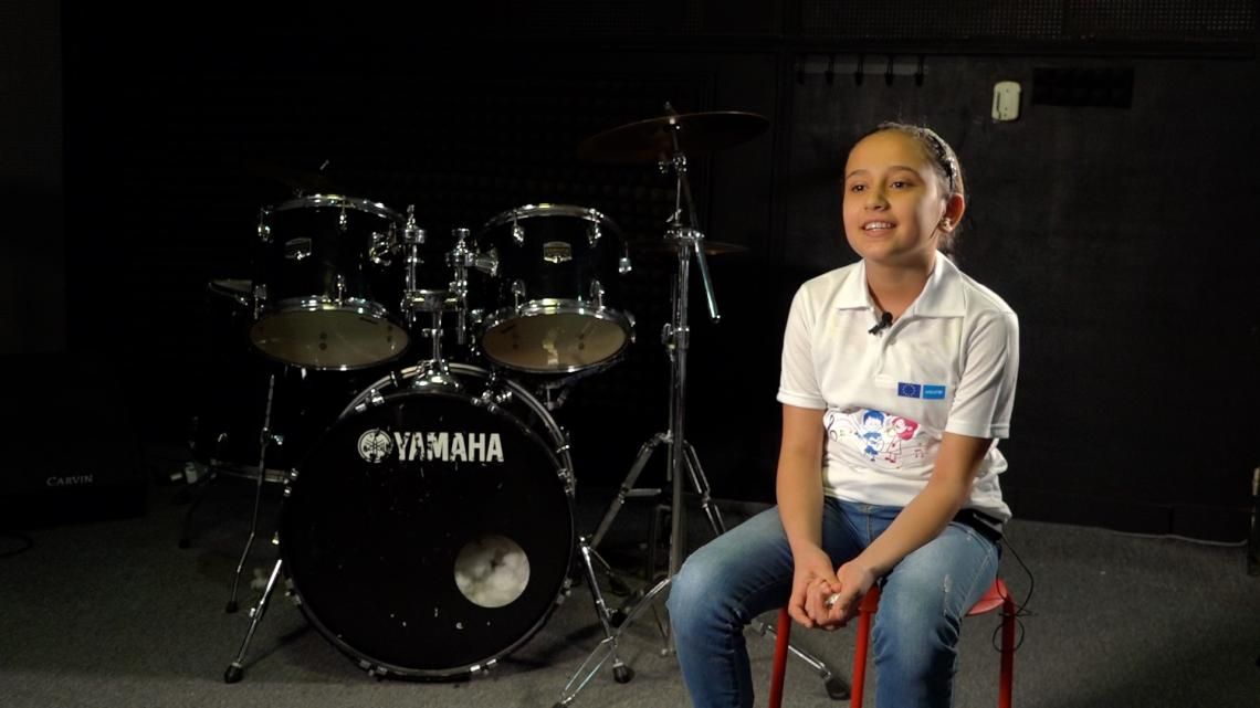 A girl sitting next to a drums set