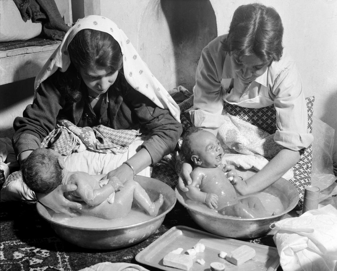 A midwife teaches a mother to bathe her twin babies