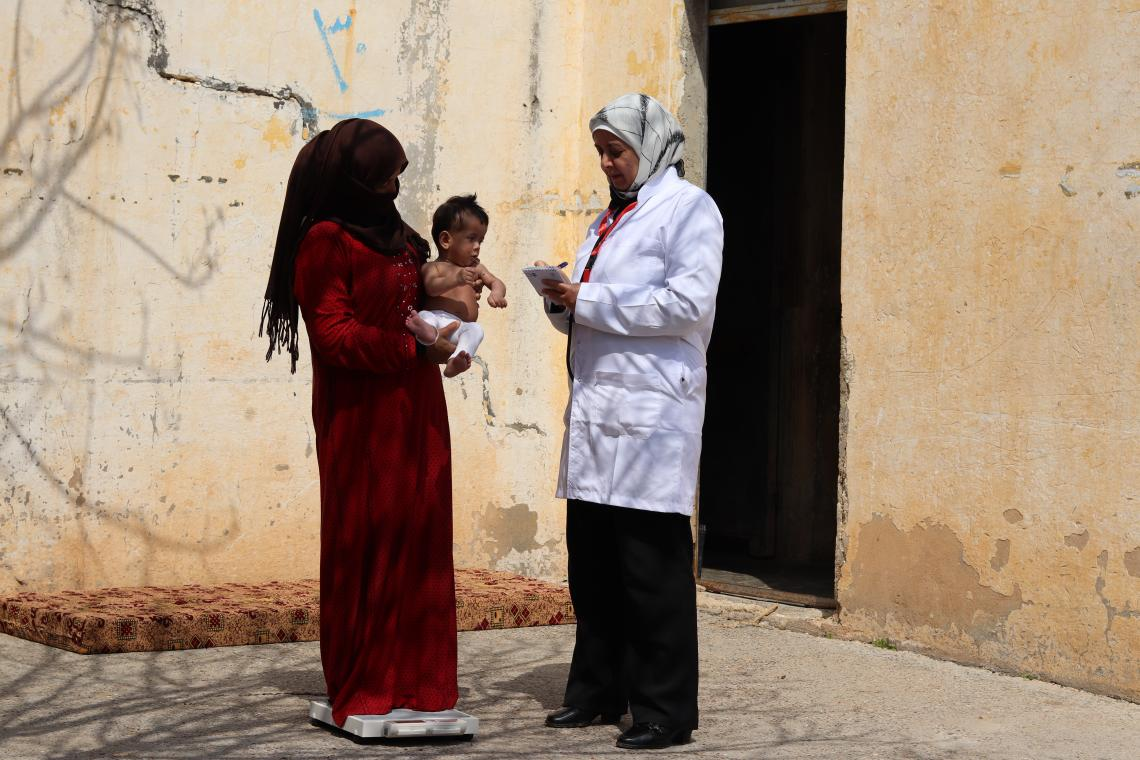 A mother with her child speaking to a doctor