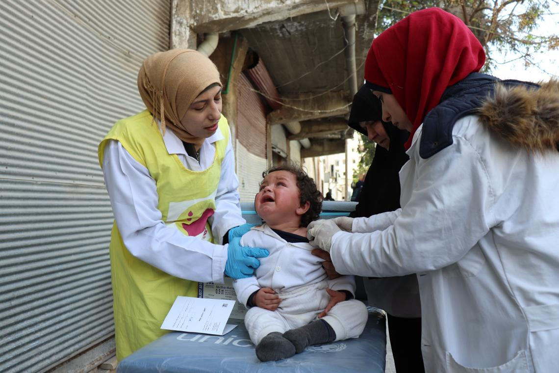 Health workers vaccinate a child while caregiver is helping them