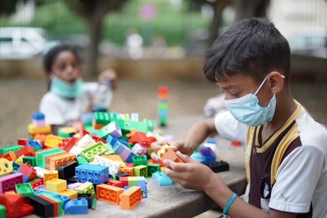 a boy wearing a face mask playing with building blocks