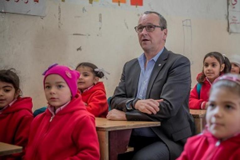UNICEF MENA Regional Director sitting in a classroom with children