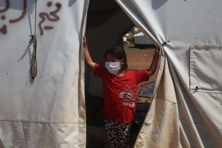 a girl with a mask looking out of a tent