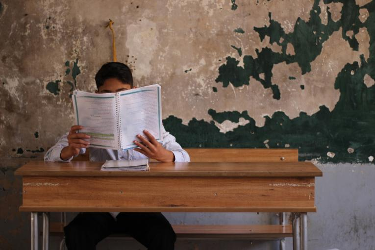 a boy reading a book in a classroom