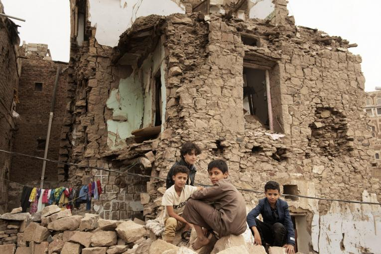 a group of kids in front of a destroyed house