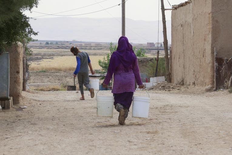 a woman and a girl carrying water buckets