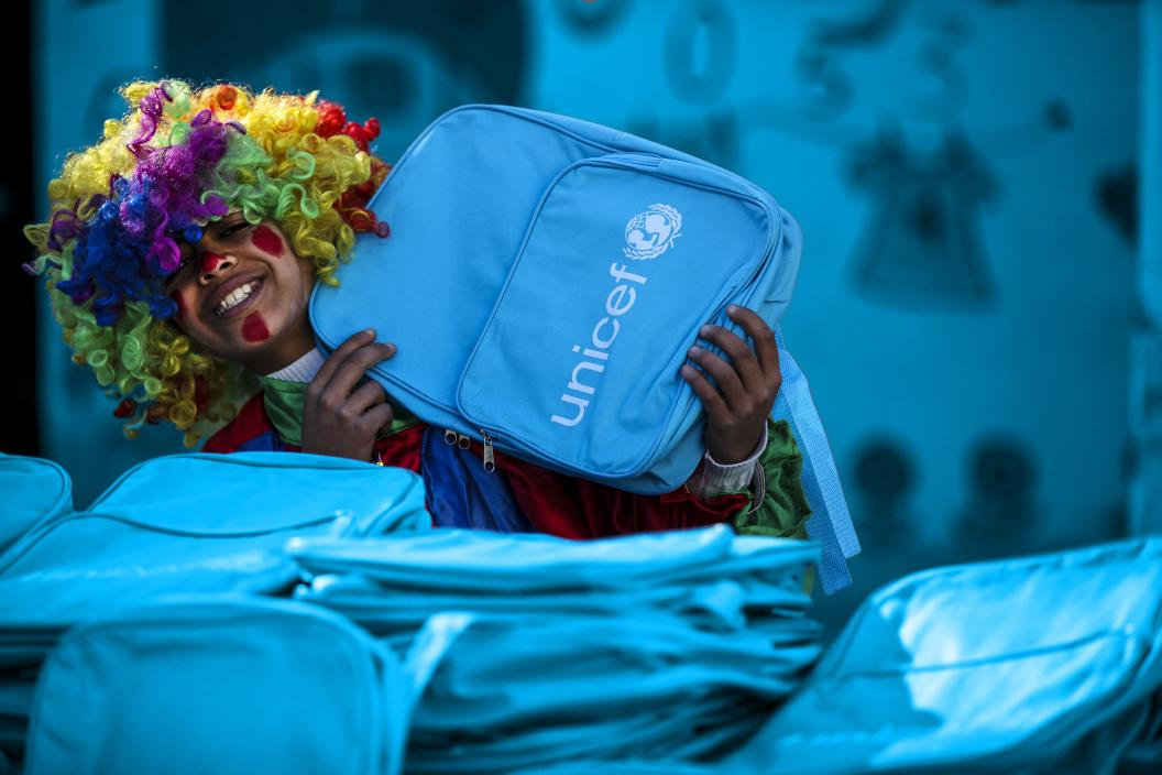 A child in clown costume holding a UNICEF school bag