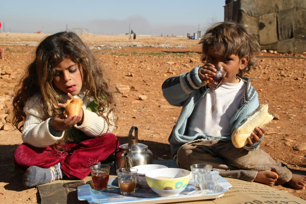 two kids eating and drinking tea outdoors