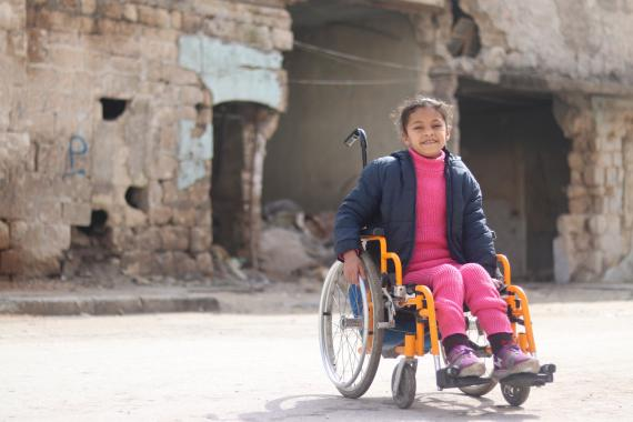 A girl on a wheelchair in front of a destructed building