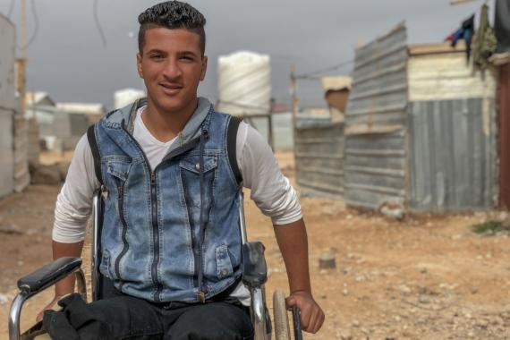 A boy on a wheelchair in a camp