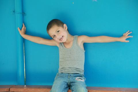 boy against a blue wall