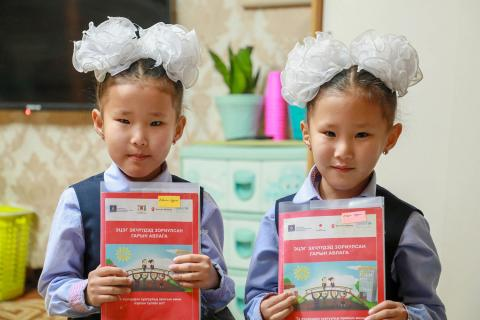 Twins holding a study guide