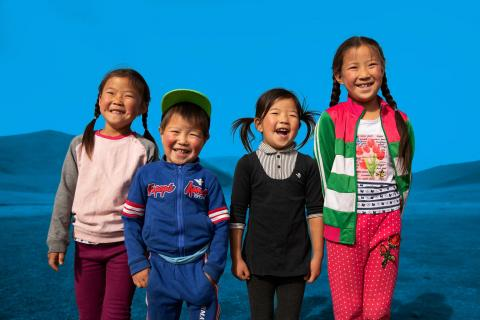 Nomin-Erdene, 7, her cousin, Anar, 4, and her sisters Nandin-Erdene, 5, and Namundari, 8, laugh outdoors in an area near their home,
