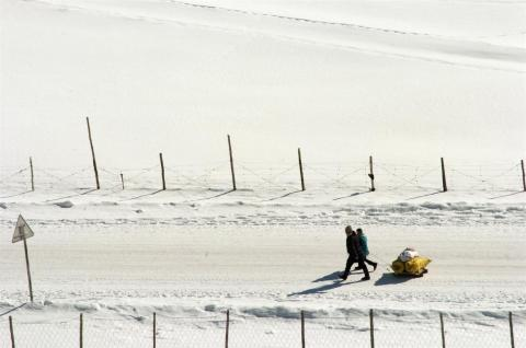 An adult and child use a sled to bring animal fodder home from the centre of Bulgan District, Khovd Province.