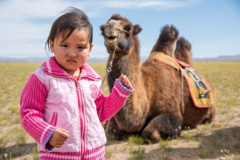 girl standing next to a camel