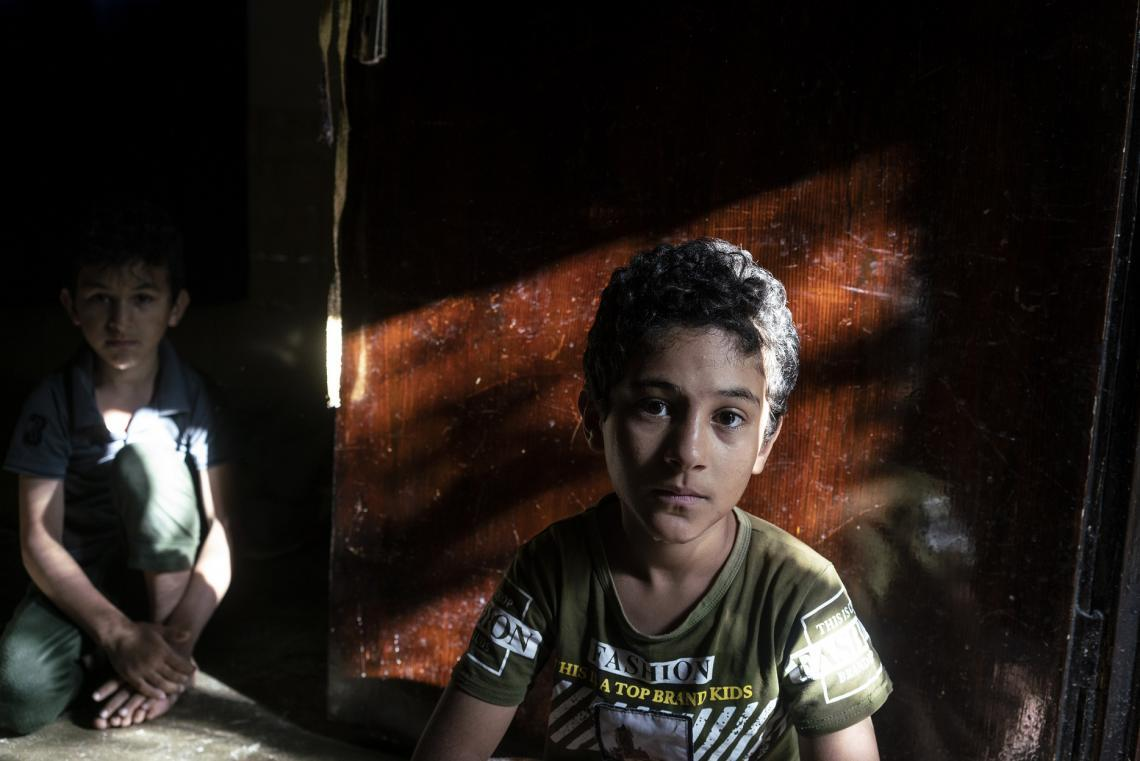 Two Syrian refugees sit on the floor of a shelter in Jordan.