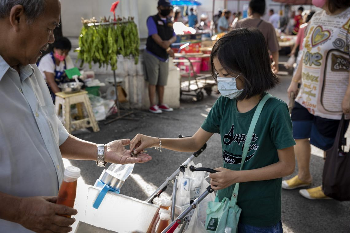A girl sells bottles of juice prepared by her grandmother at a market in Thailand.