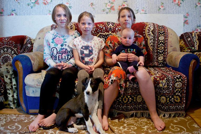 Yana, 12, Lyubov, 10, Arina, 13 and Daniil, 7 months, sit in the living room of their small rented house in Nur-Sultan, Kazakhstan.