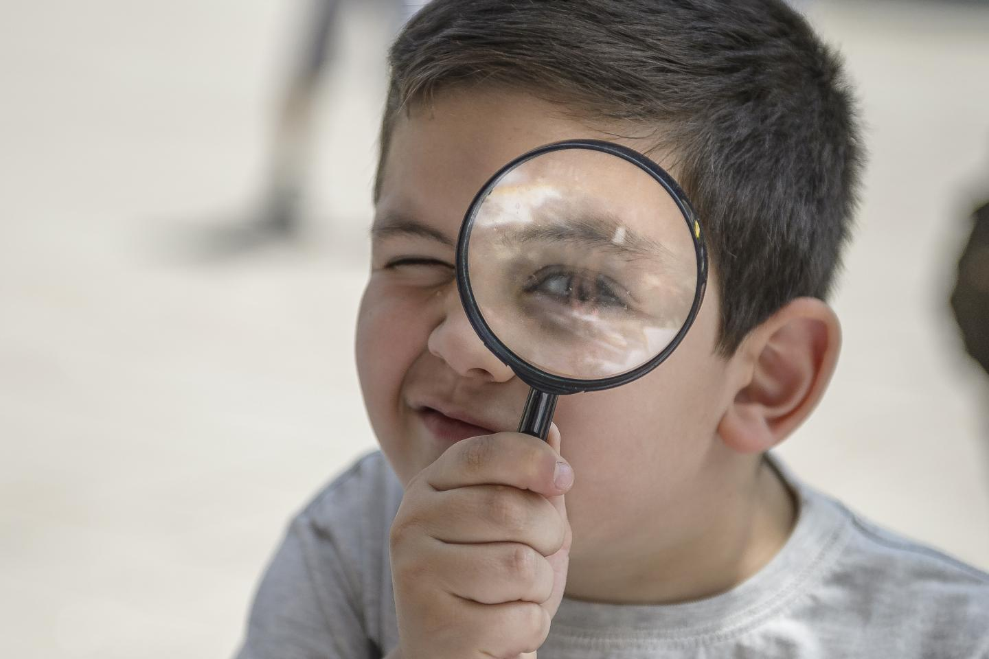 A boy looking at the camera through the magnifying glass