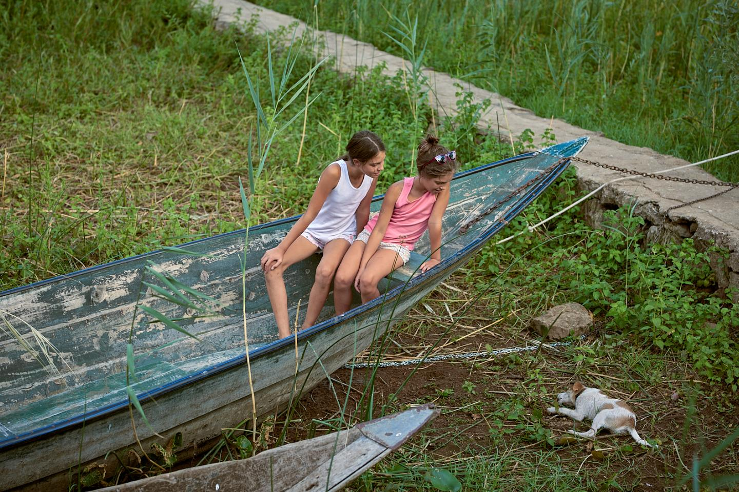 Two girls sitting in a boat on the ground watching a lying dog