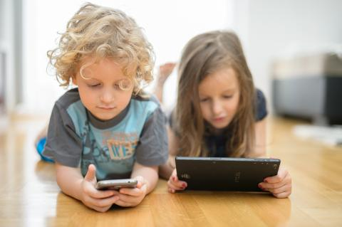 A boy and a girl lying on the floor and watching a phone and a tablet