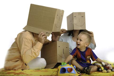 Parents with cardboard boxes on their heads playing with their child