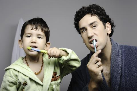 A father and a son washing their teeth