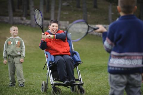 A boy in a wheelchair playing tennis with a friend