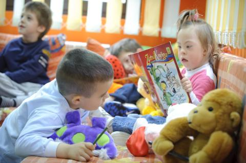 A girl with disabilities reading a book in the preschool
