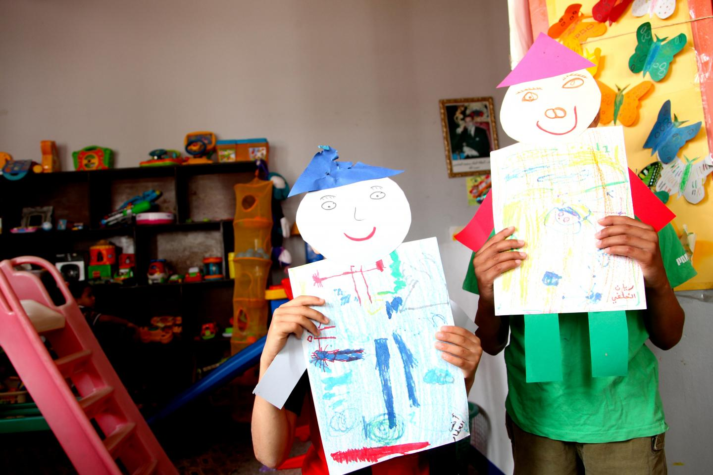 Two children holding a poster over their face