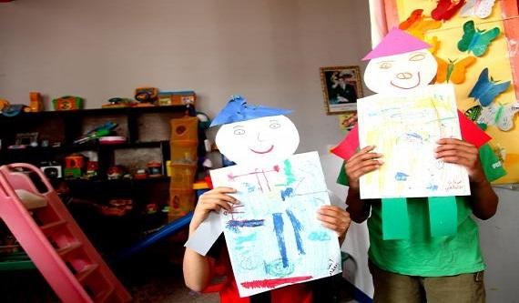 two children holding up a card above their face like a mask