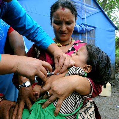 health worker administers the MR vaccine to a young child