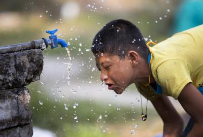A boy using water tap